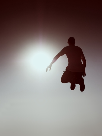 Jumping man. Young crazy man is jumping on red sky background.Silhouette of jumping man and beautiful sunset sky. Element of design. Vintage effect. Stock Photo