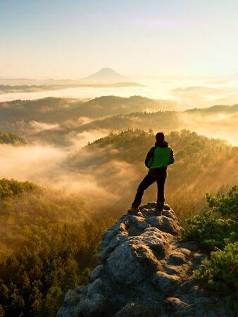 山の頂上に男。霧の谷の上の岩のピークに登ったハイカー。男は霧と霧の朝バレーの明るい朝の太陽に見守る。 写真素材