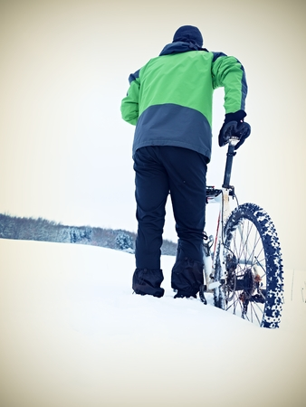 Man with mountain bike stay in powder snow. Lost path  in deep snowdrift. Rear wheel detail. Snow flakes melting on dark off road tyre.  Winter weather in the field.