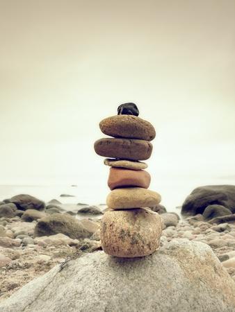 Stones pyramid symbolizing zen, harmony, balance pebbles. Ocean in background. Colorful flat stones for meditation lying on stony  sea  beach