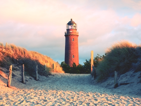 Historical lighthouse. Shinning lighthouse,  dunes and pine tree. Tower illuminated with strong warning light, dark sky in background. Lighthouse tower built from red bricks. Stock Photo