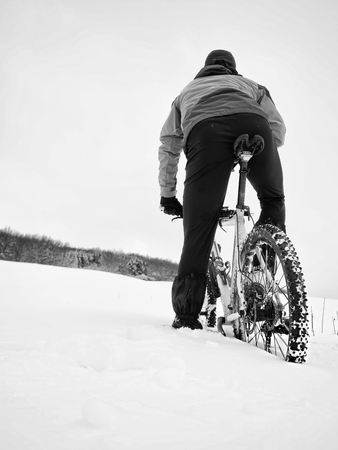 hard disk: Sportsman with mountain bike lost in snow. Lost path  in deep snowdrift.  Snow flakes melting on dark off road tyre.  Winter weather in the field.