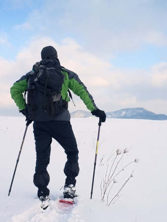 Man with snowshoes and backpack and take rest in snow. Hiker in winter jacket and trousers trekking snowshoeing in powder snow. Sunny winter day, gentle wind Brings small snow flakes Stock Photo