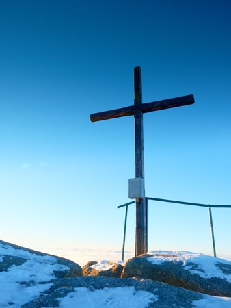 unpretentious: Winter mountain. Wooden cross on rocky mountain summit. Sharp peak covered by ice and snow.  Wooden unpretentious crucifix in memory of victims of mountains. Vivid photo.