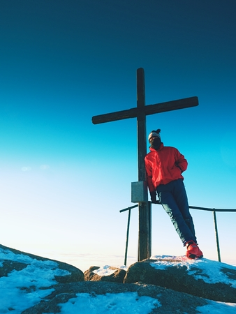 unpretentious: Man hiker in red blue winter clothes on sharp summit  with modest wooden cross.  Unpretentious crucifix  raised  on mountain peak in memory of victims of mountains. Stock Photo