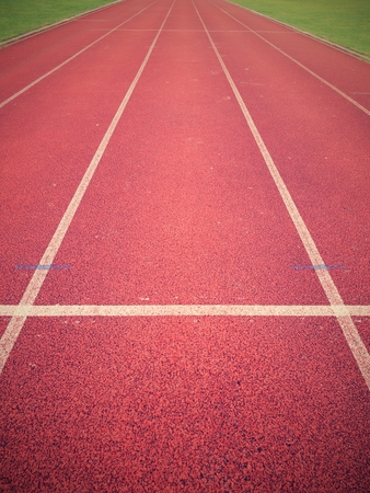 White lines and texture of running racetrack, red rubber racetracks in outdoor stadium.  Jogging track, outdoor oval stadium with a tartan track. Stock Photo