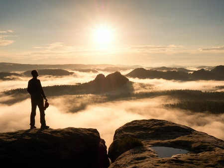 Hiker silhouette standing on rocky summit above misty valley. Nature daybreak background. Strong sun.