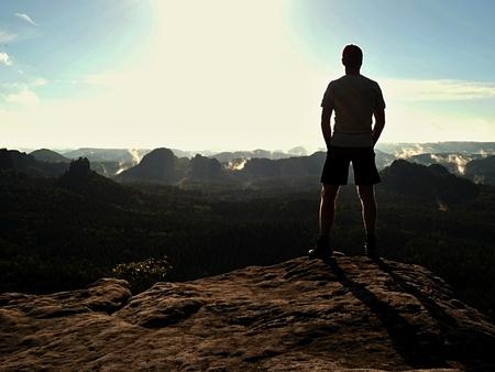 homme touristique sur la falaise de la roche dans les empires de rock parc veille sur la brume crémeuse et la vallée brumeuse du matin au Sun