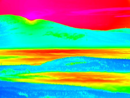 Animal view. Infrared scan of hilly landscape, pine forest with colorful fog, hot sunny sky above. Grunge background in amazing thermography colors. Stock Photo