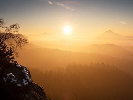 inversion: Red daybreak. Misty sunrise in the mountains, the gradation of color clouds. Misty daybreak in a beautiful hills. Peaks of hills are sticking out from foggy background, the fog is red and orange