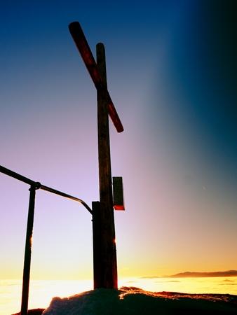 unpretentious: Modest wooden cross raised  on rocky mountain summit . Sharp snowy peak. Daybreak Sun in sky. Wooden unpretentious crucifix in memory of victims of mountains. Vivid photo.