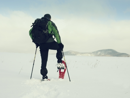 Winter tourist checking snowshoe. Hiker in green winter jacket and carry a big backpack walk in snowy filed. Snowshoeing in powder snow.