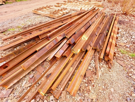 Heap of rusty rails in junkyard. Stock of steel rails from closed railway station.  Metal material is waiting for transport to steel foundry for recycling Stock Photo