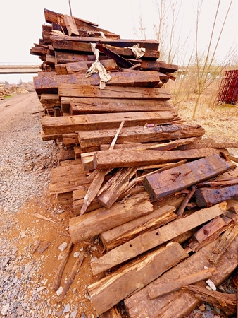 Terrible smell Extracted pile of old wooden ties. Old Used oiled oak railway sleepers Stored after big reconstruction of old railway station.