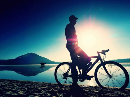 Silhouette of sportsman  holding bicycle on lake beach, colorful  sunset cloudy sky in background and reflection in smooth water level
