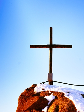 Modest wooden cross raised  on rocky mountain summit . Sharp snowy peak. Daybreak Sun in sky. Wooden unpretentious crucifix in memory of victims of mountains. Vivid photo.