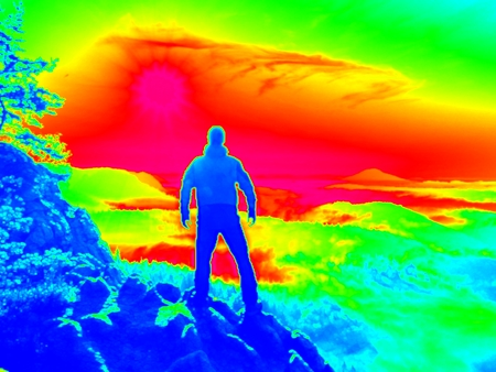 Man on rock. Fantastic infrared scan. Tourist on the rocky peak. Daybreak in mountains, heavy mist in deep valley in colors of ultra violet measurement