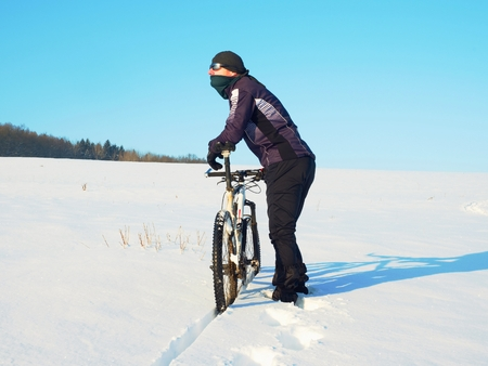 Biker pushing mountain bike on snow drift. Freeze sunny winter weather. Biker is pushing bike in deep snow in meadow. Amazing sunny day. Small snow flakes in the air Stock Photo