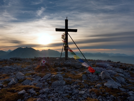 Big wooden cross at mountain peak in wind with Buddhist praying flags.  Cross on top of a mountains peak as typical in the Alps. Monument to the dead climbers
