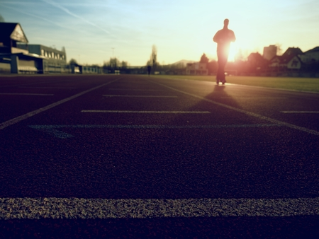 Marathon man training.  Sportsman in running clothes on stadium at sunset. Sport and healthy lifestyle concept and jogging civic training workout