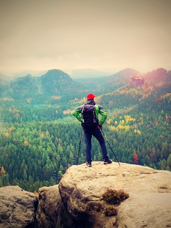 nad: Tourist guide on the summit with poles in hand and heavy backpack. Hiker green jakcet nad red cap stand on rocky view point above misty valley. Sunny spring daybreak in rocky mountains.