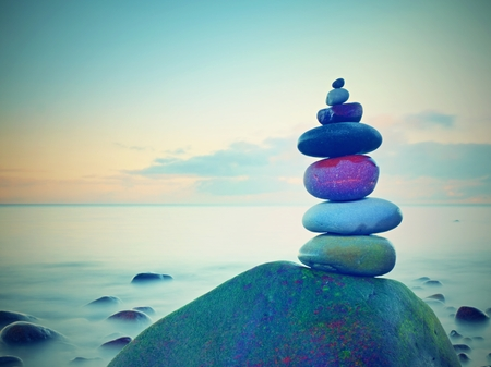 Stacked rounded stones at sea. Small polished pebbles stack on dark wet rock,  blue smooth water of ocean in background