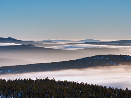 Misty valley in winter mountains. Peaks of  mountains above creamy mist.  Inverse weather, shinning fog. Stock Photo