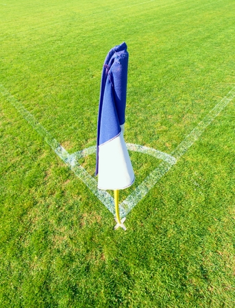 jugueria: White blue flag in corner of football playground, lazy wind blowing Foto de archivo