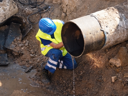 wire: Worker underground with hand grinder is cutting big metal tube. Sparks are flying down to wet clay. Working staff in safety clothes, helmet, protective boots. Deep excavation pit. Stock Photo