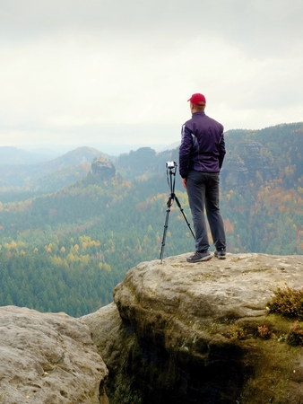 Outdoor photographer with tripod and camera on a rock thinking. Creamy autumnal mist in valley bellow. Dreamy rocky mountains. Misty sunrise in a beautiful valley Stock Photo
