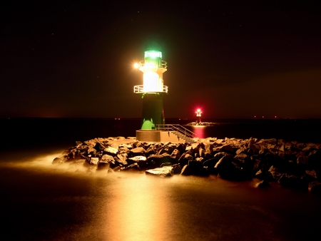 Green lighthouse in Warnemunde shinning at the end of stony pier in the dark night Stock Photo