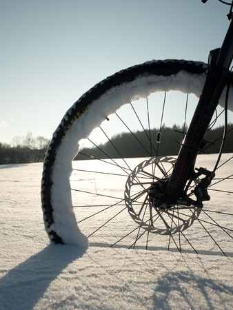 The front wheel of mountain bike jab in powder snow. Lost path under deep snowdrift. Snowflakes melting on dark off road tyre.  Winter weather in the field.