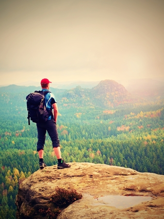 Tourist with big backpack stand on rocky view point and watching to colorful autumnal landscape. Tourist traveler on view point.  Hiker looking  horizon in trip in  fall country Stock Photo