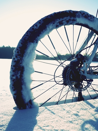 Mountain bike stay in powder snow. Lost path  in deep snowdrift. Rear wheel detail. Snow flakes melting on dark off road tyre.  Winter weather in the field.