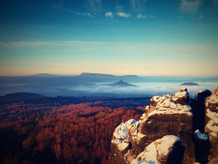 Freeze autumn trek, rocks covered with first  fresh snow. Stony rock peak above foggy valley. Winter misty sunrise in a beautiful rocks empire. Stock Photo