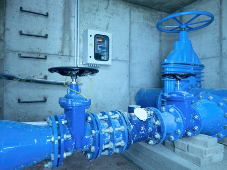City potable water pipeline in concrete shafts with 500mm Gate valve, 250mm armature  branch.  The dring water service and Water network maintenance. Stock Photo