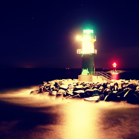 shinning: The ighthouse shinning at port gate. Modern light house at the end of stony pier in the dark night. Warnemunde on the Baltic Sea at the harbor entrance, Germany Stock Photo