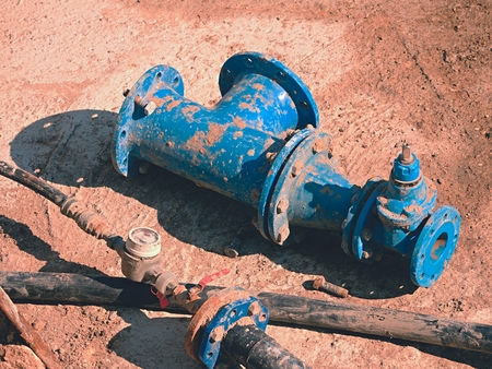 Old drink water pipes, used blue gate valve reduction and joint members. Water supply interrupted, repairing of infrastructure. Metal corrosion texture. PVC pipeline. Imagens