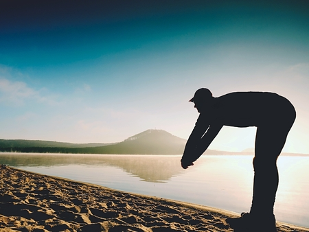 Man exercising on the beach.  Silhouette of active man exercising  and stretching on the lake beach at sunrise. Healthy lifestyle. Alone young fitness man exercise  at morning beach