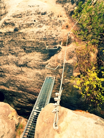 Iron ramp in rock, tourist ladder. Iron twisted rope fixed in block by screws snap hooks. The rope end anchored into sandstone rock. Climbers way via ferrata. Stock Photo