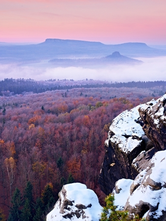 First powder snow cover on sandstone rocks above valley park. Heavy mist in valley bellow view point. Chilly autumnal foggy weather bellow. Stock Photo