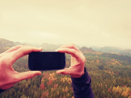 Black phone display. Dark mobile screen. Man hands takes photos with smart phone on peak of rock empire. Dreamy fogy landscape, spring pink misty sunrise in valley of rocky mountains.
