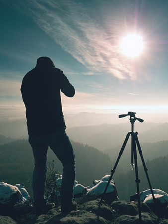 documenting: Professional nature photographer do work on snowy cliff.  Man takes photos with mirror camera on peak of rock. Dreamy fogy landscape, spring orange pink misty sunrise.