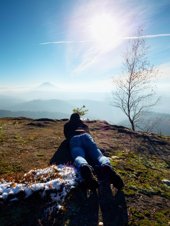 inversion: Man lay down and taking photo by mirror camera on neck. Snowy rocky peak of mountain. Professional photographer Takes photos with mirror camera on snowy peak of rock.