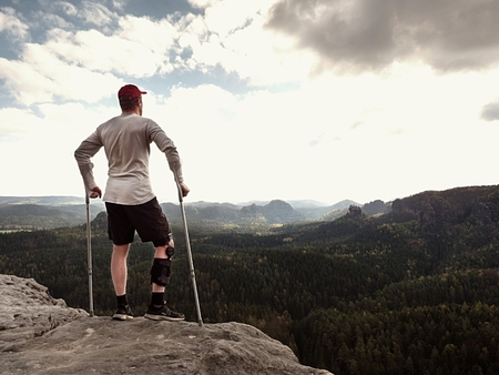 immobilize: Hiker in grey t-shirt, medicine crutch and  leg fixed in immobilize achieved mountain peak. Man has fixed  broken leg in immobilizer Deep misty valley bellow of manr. Spring sunny day