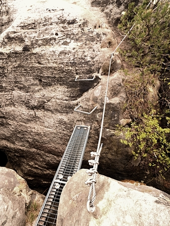 Steel ladder way, steel ramp between rocks via ferrata. Iron twisted rope fixed in block by snap hooks. The rope end anchored into sandstone rock.