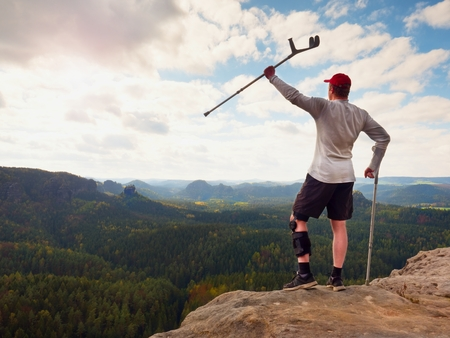Happy tourist with forearm crutch above head reached mountain peak. Hiker with hurt knee in immobilizer and medicine poles hold hand in air. Colorful forests in valley below