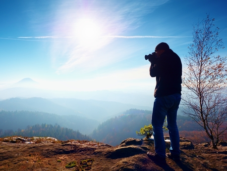 Tall Man is taking photo camera on the mirror neck. Snowy rocky peak of mountain. Professional photographer Takes photos with mirror camera on snowy peak of rock.