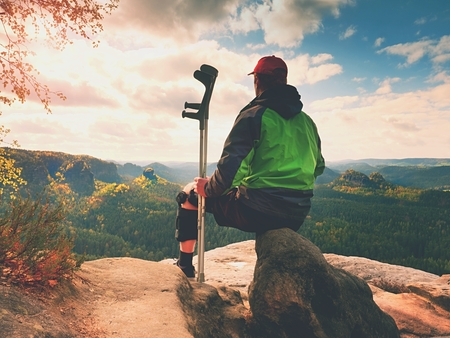 Tired man tourist  sit with  hurt knee in immobilizer or rock, hold  medicine pole.  Open forest landscape, long valley bellow cliff.
