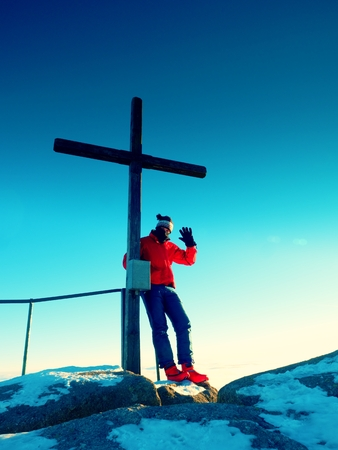 unpretentious: Tourist in red blue winter clothes on sharp summit  with modest cross.  Winter Sun in sky. Wooden unpretentious crucifix  raised  on mountain peak in memory of victims of mountains. Stock Photo